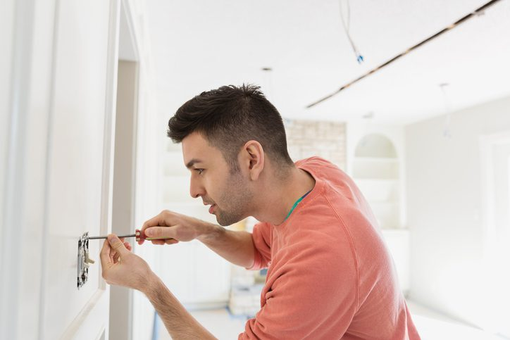 Polk Electric LLC | Young man installing light switch at home