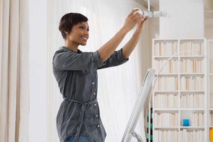 Polk Electric LLC | Woman fitting lightbulb